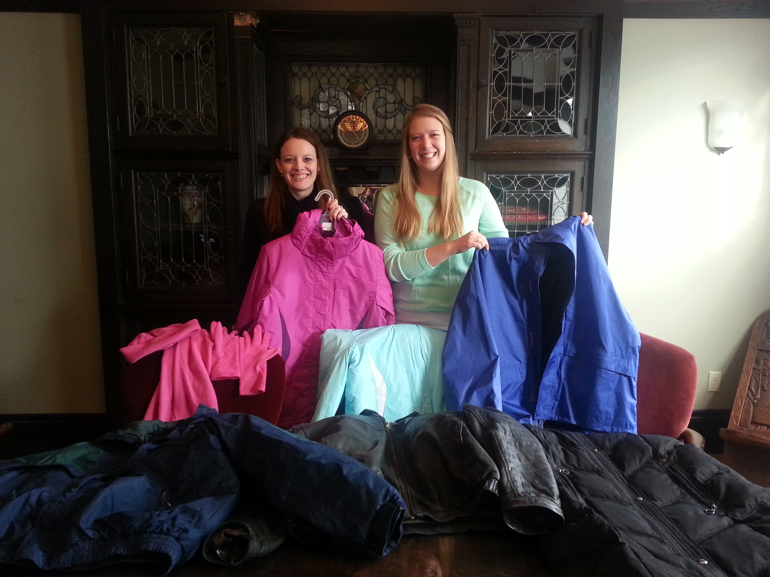CVT staff Casie and Emily with coats donated by Kroll Ontrack